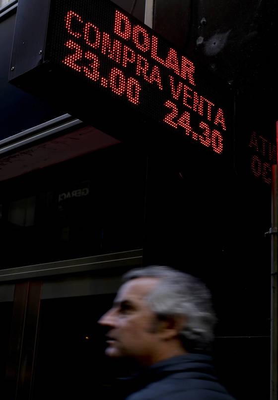 11일(현지시간) 아르헨티나 부에노스아이레스 시내. 미국 달러화 급등과 아르헨티나 페소화 급락을 알리는 전광판 아래를 현지 시민이 지나가고 있다. [AP=연합뉴스]