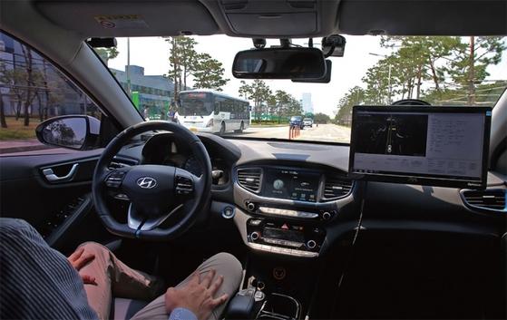 AI가 운전을 대신하는 자율주행차의 내부 모습. 운전자가 핸들과 브레이크에서 손발을 뗀 채 차가 달리고 있다.
