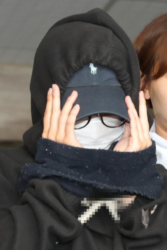 홍익대 남성 누드모델의 나체를 몰래 찍어 워마드에 유포한 혐의를 받고 있는 안모씨가 12일 오후 서울 마포구 마포경찰서에서 나와 영장실질심사를 받기 위해 서부지방법원으로 이송되고 있다. [뉴스1]