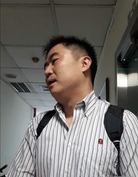 """싱가포르 북한대사관 직원이 14일 취재진에게 """"돌아가달라""""며 취재 거부를 하고 있다.         싱가포르=전수진 기자"""