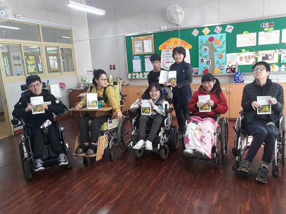 대구보건학교 학생들과 박호숙 교사가 책을 들고 기념사진을 찍었다. [사진 대구보건학교]