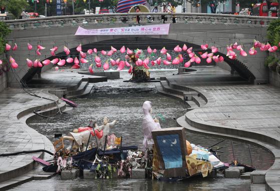 서울과 수도권을 비롯한 중부지방에 폭우가 내린 16일 서울 중구 청계천 모전교 인근에 수문개방으로 떠밀려온 전통등 조형물이 쓰레기와 함께 다른 전시물에 걸려있다. 이곳에서는 오는 22일까지 부처님오신날 맞이 제11회 청계천 전통등 전시회가 열리고 있었다. [연합뉴스]