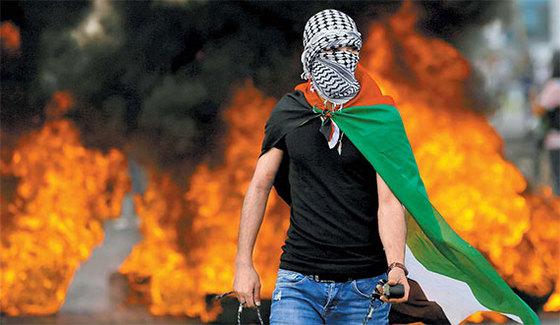 한 팔레스타인 주민이 15일 요르단강 서안 라말라 인근의 유대인 정착지에서 미국대사관의 예루살렘 이전에 항의하는 시위를 하고 있다. [로이터=연합뉴스]