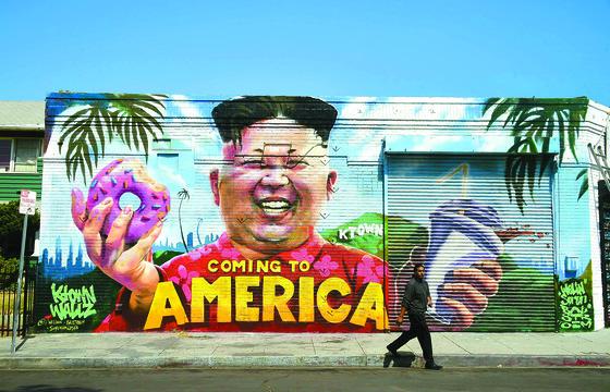 북·미 정상회담을 한 달여 앞둔 14일(현지시간) 미국 로스앤젤레스 거리에 있는 김정은 북한 국무위원장 벽화 앞을 한 시민이 지나가고 있다. 김 위원장이 도넛과 음료를 든 채 활짝 웃고 있는 이 벽화는 도시 외벽 그림으로 사회를 풍자하는 단체 '케이타운 월즈(Ktown Wallz)'의 작품이다. [AFP=연합뉴스]