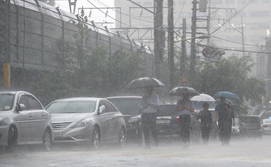 폭우가 쏟아진 16일 서울 한 도로에서 시민들이 발걸음을 서두르고 있다. [연합뉴스]