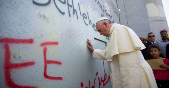 지난 2014년 5월 25일 중동 순방 당시 프란치스코 교황이 팔레스타인 영토인 요르단강 서안지구 베들레햄에서 미사 장소로 이동하던 중 이스라엘과 서안지구를 구분하는 분리장벽 앞에서 기도를 올리고 있다. 당시 교황이 기도를 올린 8m 높이의 이 장벽의 벽면에는 '팔레스타인에 자유를'이라는 글귀가 새겨져 있었다. [AP=연합뉴스]