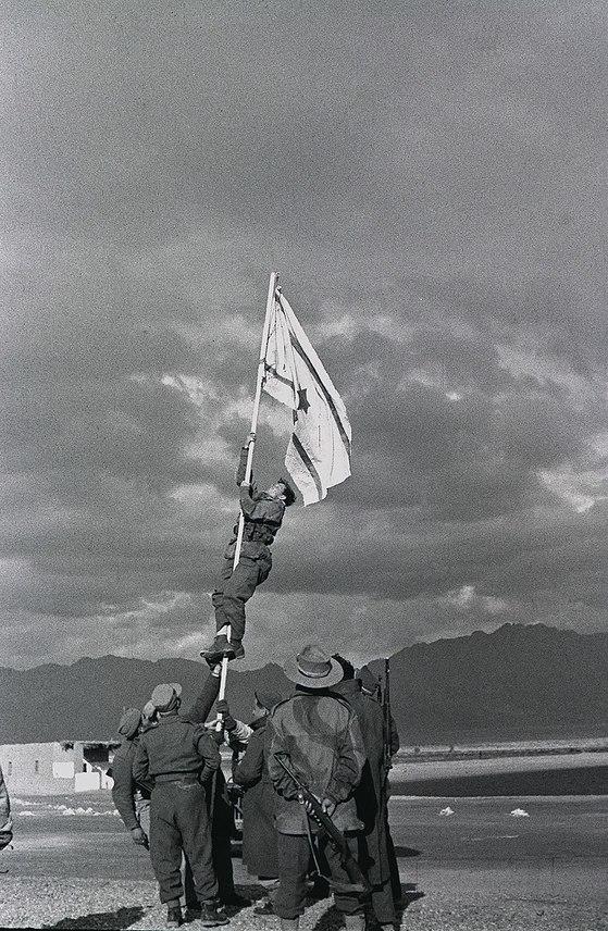 1947년 이스라엘의 남쪽 끝인 아카바만 연한 항구도시인 에일라트를 점령한 시오니스트 무장대원들이 잉크로 그린 국기를 게양하고 있다. 이스라엘 독립을 상징하는 사진이다. [중앙포토]