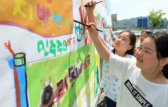 지난 9일 전북 전주만성초 학생들이 전북도선관위 선거버스의 현수막에 색칠을 하고 있다. [뉴스1]