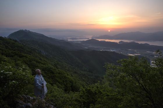 여명이 밝아오는 아침 무렵 미황사 주지 금강스님이 달마산 트레킹 코스 달마고도를 걷고 있다. 달마고도에서 내려다보이는 다도해가 아침노을로 물들었다