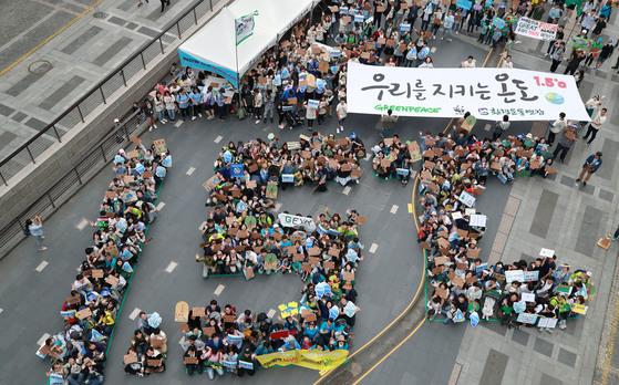 그린피스, 세계자연기금(WWF), 환경운동연합 주최로 20일 오후 서울 청계광장에서 '기후행진 2018' 행사가 열렸다. 참가자들이 파리협정에서 약속한 지구 평균 온도 상승 1.5℃ 이내 유지 목표 이행을 촉구하며 '1.5℃' 글자 모양을 만들고 있다. 변선구 기자