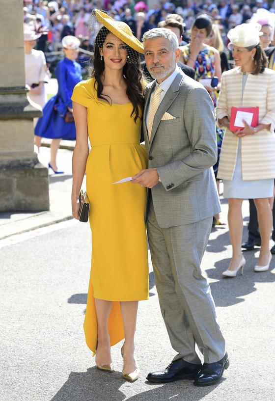 지난 19일 열렸던 해리 왕자와 메건 마클의 결혼식에 참석한 클루니 부부. 인권 변호사로 활동하고 있는 아말 클루니와 영화배우 조지 클루니는 '노란색'을 공통으로 한 커플 패션을 선보여 화제를 모았다. [AP=연합뉴스]