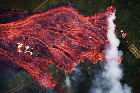 19일(현지시간) 미국 하와이 킬라우에아 화산에서 분출된 용암이 빠른 속도로 흘러내리며 파호아 지역의 주택을 덮치고 있다. [EPA=연합뉴스]