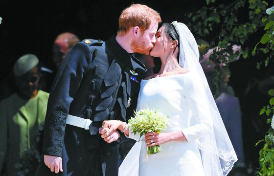 지난 19일(현지시간) 영국 윈저성 세인트 조지 채플에서 결혼식을 마치고 나와 시민들 앞에서 첫 '웨딩 키스'를 선보이고 있는 해리 왕자(왼쪽)와 메건 마클. [UPI=연합뉴스]
