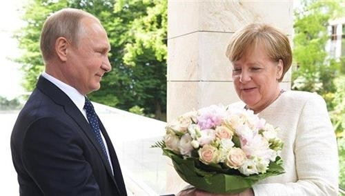 지난 18일 소치를 방문한 메르켈 총리(오른쪽)에게 꽃다발을 선물하는 푸틴 대통령 [리아노보스티=연합뉴스]