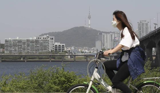 중국발 황사의 영향으로 전국의 미세먼지 농도가 '나쁨'을 보인 지난해 5월 7일 서울 여의도 한강공원에서 시민이 마스크를 쓰고 자전거를 타고 있다. [중앙포토]