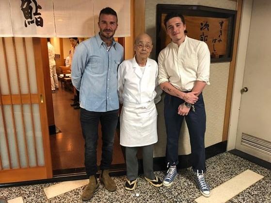 데이비드 베컴(왼쪽)과 장남 브루클린(오른쪽) 부자가 일본 도쿄의 유명 스시집 '스키야바시 지로'를 방문해 스시 장인 오노 지로(가운데)씨와 함께 기념촬영을 했다.              [브루클린 인스타그램]