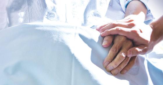 한 대학병원 중환자실에서 의료진이 말기환자의 손을 잡고 있다.[중앙포토]