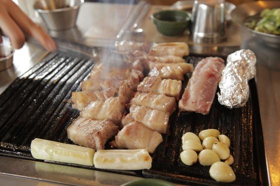 금돼지식당의 대표메뉴 '본삼겹'. 2주간 저온숙성한 돼지고기를 갈빗대에 붙은 채 내놓기 때문에 육즙이 풍부한 삼겹살과 갈빗대에 붙은 쫄깃한 식감의 고기를 함께 맛볼 수 있다.