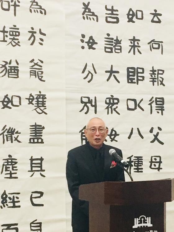 """지난 18일 서울 예술의전당 서예박물관에서 대작 '부모은중경' 전시작을 배경으로 인사하는 하석 박원규씨. 하석은 ' 붓을 든 지 55년, 돌아보니 어머니의 큰 사랑으로 그 힘겨운 세월을 이겨왔다""""고 말했다."""
