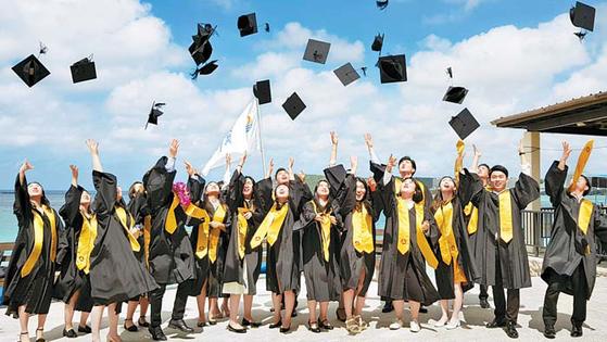 지난 2월 미국 PIC괌리조트에서 열린 백석대의 '찾아가는 졸업식'에서 학생들이 학사모를 던지며 환호하 고 있다. 해외 취업으로 졸업식에 참여하지 못한 학생들을 위해 대학 관계자가 준비한 행사다. [사진 백석대]