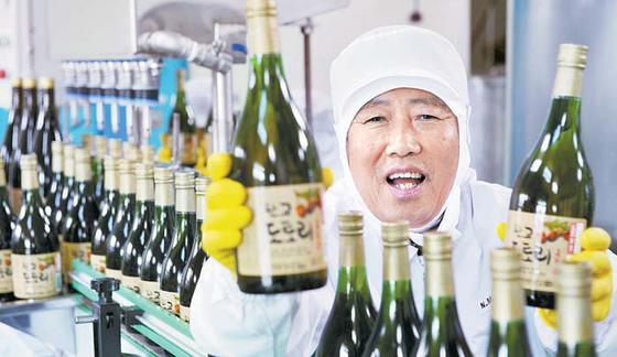 충남 서천 농민식품 김영근 대표는 도토리 진액, 도토리 묵 등 각종 가공식품을 만든다. 그는 2016년 '대한민국 식품 명인'으로 지정됐다. 김씨가 양조장에서 도토리 술을 들고 웃고 있다. [중앙포토]