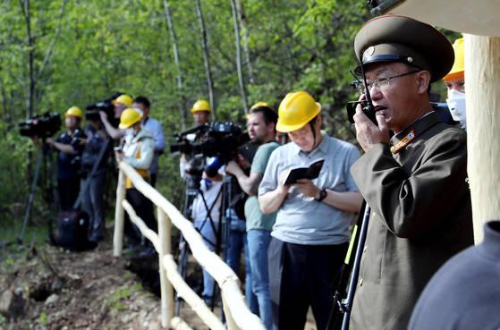 24일 북한 핵무기연구소 관계자들이 함경북도 길주군 풍계리 핵실험장 폐쇄를 위한 폭파 작업을 했다. 핵무기연구소 관계자가 갱도 폭파에 앞서 무선 교신을 하고 있다. [사진공동취재단]