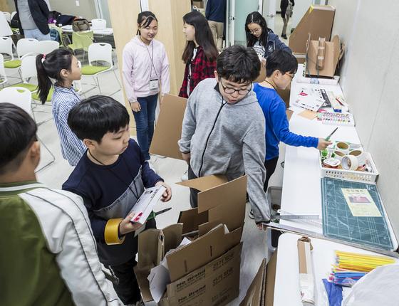 영메이커 프로젝트 시즌 4 참여자들이 종이상자를 활용한 만들기를 하기 위해 재료를 고르고 있다.