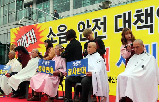 지난달 5일 경남 김해시청 앞에서 열린 '소음·안전 대책없는 김해 신공항 반대 시민 행동의 날' 집회에서 신공항 결사 반대를 주장하며 삭발하고 있는 모습 [연합뉴스]