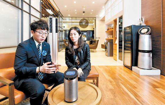서울 청담동 LG전자 베스트샵 강남본 점에서 기자(오른쪽)가 LG 씽큐 허브를 체험하기 전 사용 설명을 듣고 있다.