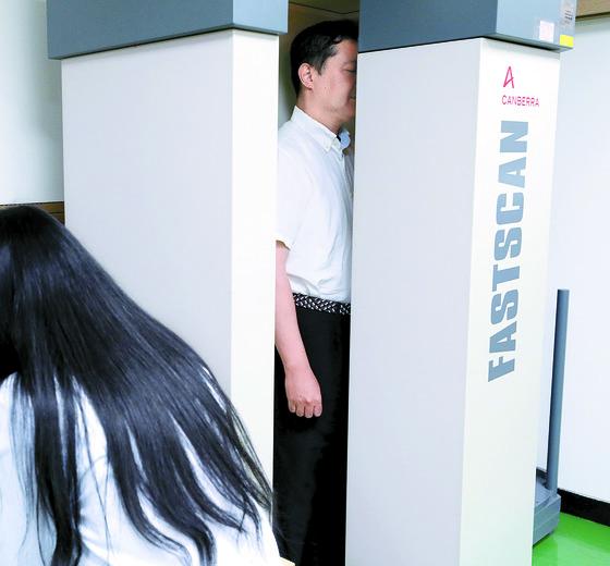 북한 풍계리 핵실험장 폐기 행사를 취재하고 돌아온 한국 취재단이 28일 서울 공릉동 원자력병원 국가방사선비상진료센터에서 방사선 피폭 여부를 판별하기 위한 전신계수검사를 받고 있다. [사진공동취재단]