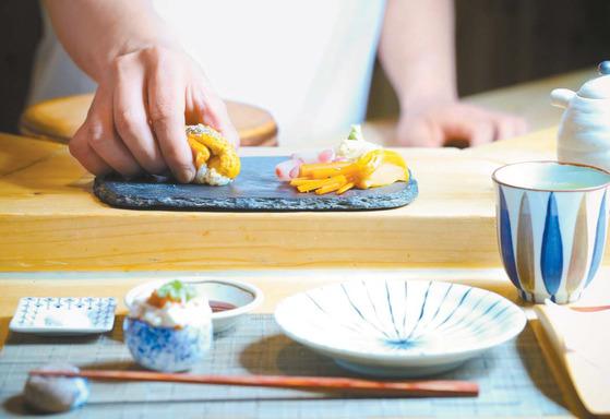 '오마카세'란 그날의 음식을 셰프에게 일임한다는 의미로 셰프의 창조력과 신뢰를 기본으로 한다. 한남동 '스시쵸우' 박진태 셰프가 방금 만든 스시를 바의 손님에게 접대하고 있는 모습.