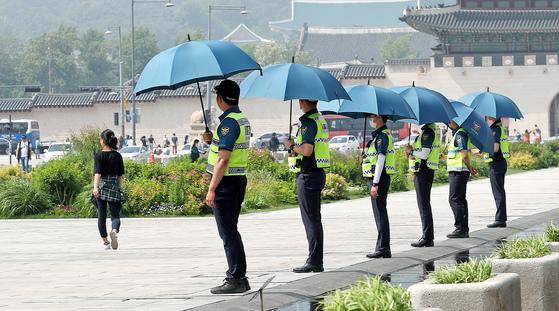 28일 광화문광장에서 근무 중인 경찰들이 햇볕을 가리기 위해 우산을 쓰고 있다. [뉴스1]