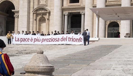 한국 태권도시범단이 30일(현지시간) 바티칸 성베드로 광장에서 시범 말미에 '평화가 승리보다 더 소중하다(Pace e' piupreziosadeltrionfo)'는 문구를 이탈리아어로 적은 현수막을 펼쳐 보이고 있다. [EPA=연합뉴스]
