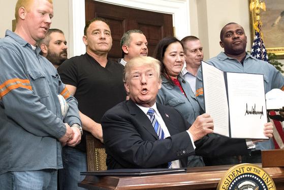 도널드 트럼프 미국 대통령이 지난 3월 8일(현지시간) 백악관 루스벨트룸에서 철강 노동자들이 지켜보는 가운데 외국산 철강 및 알루미늄 제품에 고관세를 부과하는 행정명령에 서명했다. [UPI=연합뉴스]