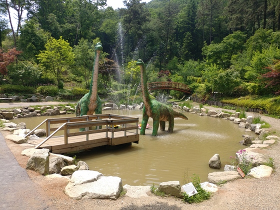 경기도 이천시 마장면 덕평공룡수목원 초입에서 초식공룡인 세이스모사우루스 모형이 연못에 발을 담그고 있다. 뒤로 푸르른 숲이 보인다.