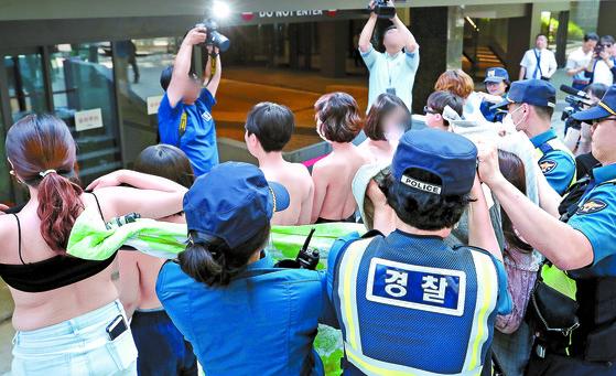 """'불꽃페미액션' 회원들이 지난 2일 서울 강남구 페이스북코리아 앞에서 상의 탈의 시위를 하고 있다. 이들은 '페이스북은 여성의 나체 사진은 음란물로 규정해 삭제하면서 남성의 나체 사진은 삭제하지 않는다. 이런 차별은 없어져야 한다""""며 '남성의 나체를 허용하는 것처럼 여성의 나체도 허용해야 한다""""고 주장했다. [연합뉴스]"""