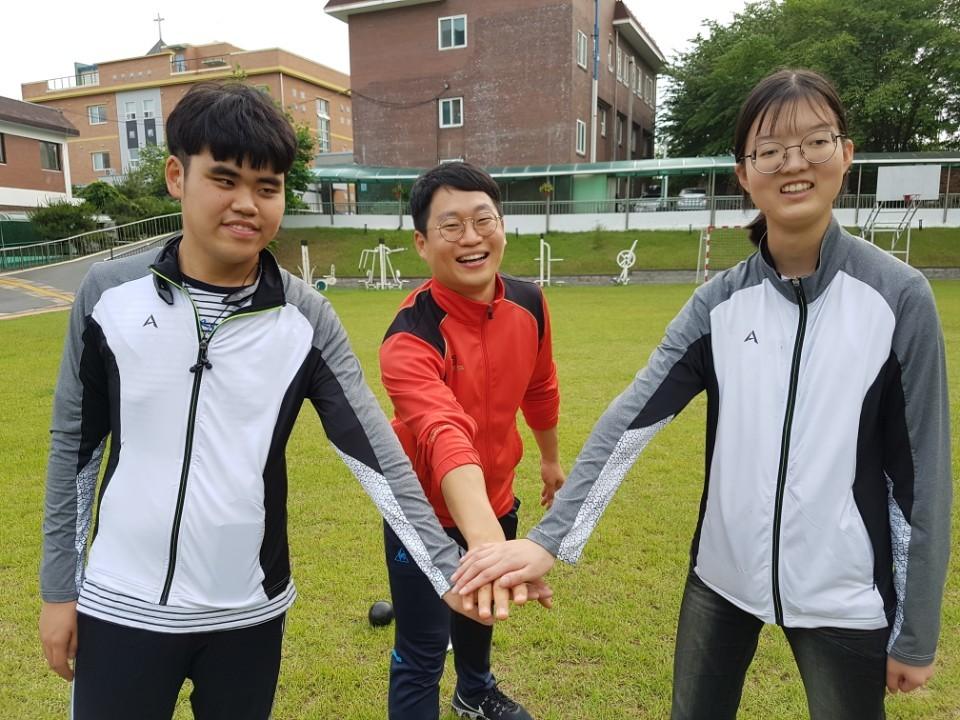 전북맹아학교 운동장에서 고등학교 2학년인 박소영(17)양과 김명찬(18)군이 박성준(34) 체육교사와 함께 기념 촬영을 하고 있다. 박양은 최근 충북 충주에서 끝난 '제12회 전국장애학생체육대회' 여고부 원반던지기와 포환던지기에서 금메달을 따내며 2관왕에 올랐다. 김군도 같은 대회 남고부 원반던지기·포환던지기에서 은메달 2개를 거머쥐었다. 익산=김준희 기자