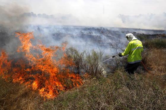 가지지구 시위대가 연에 인화성 물질을 달아 날려보내 이스라엘 들판에 화재가 발생했다. 이스라엘 소방관 등이 불을 끄고 있다. [EAP=연합뉴스]
