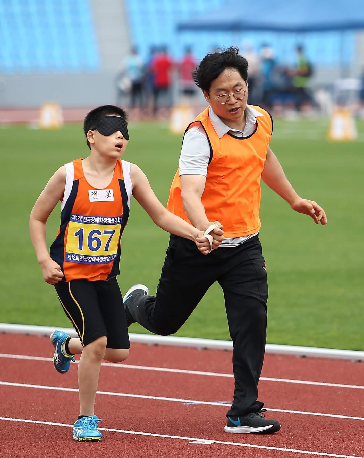 전북맹아학교 중학교 1학년 이석호(13)군이 '제12회 전국장애학생체육대회' 남중부 육상 100m 결승에서 가이드로 나선 박성준(34) 체육교사와 함께 뛰고 있다. 이군은 이 경기에서 제일 먼저 골인해 금메달을 땄다. [사진 전북맹아학교]