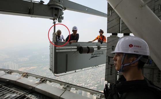 서울 송파구 롯데월드타워 외벽을 맨손으로 오르던 프랑스인 등반가 알랭 로베르(56)가 건물에 설치된 곤돌라를 타고 126층 옥상으로 올라오고 있다. [롯데물산 제공]