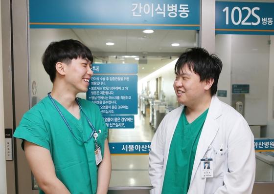 자신의 간을 아버지에게 기증한 아들들이 이제는 이식수술을 한 서울아산병원의 다른 간 이식 환자를 돌보는 의사와 간호사가 됐다. 오른쪽이 최진욱 임상강사(외과 전문의), 형민혁 간호사. [서울아산병원 제공]