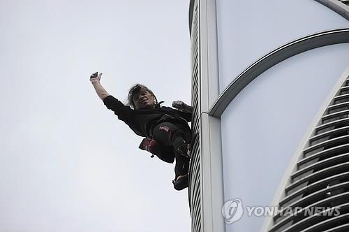 6일 롯데월드타워를 오르던 알랭 로베르가 손을 흔들고 있다. [연합뉴스]
