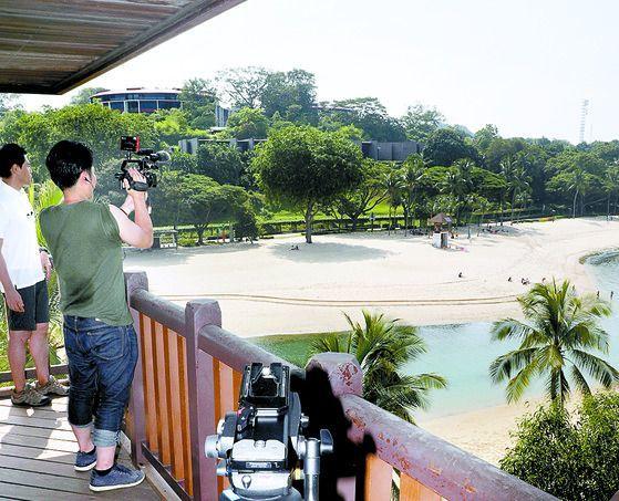 외신 기자들이 6일 오후 싱가포르 센토사 섬 팔라완 비치 전망대에서 북·미 정상회담 장소인 카펠라 호텔(왼쪽 위)을 취재하고 있다. [연합뉴스]