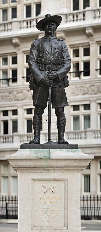 영국 런던의 국방부 앞에 서 있는 구르카족 병사의 동상. '용감한 병사 중에 가장 용맹한 군인'이라는 별명으로 불렸다 전통 단검인 쿠크리를 2개 겹쳐 놓은 구르카족 상징물이 보인다. [위키피디아]