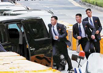 북한 경호원들이 김정은 국무위원장이 탑승한 차량 행렬 주위에서 이동하고 있다. [로이터=연합뉴스]
