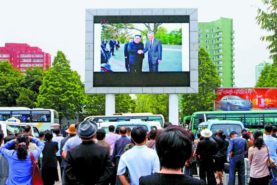 북한 주민들이 11일 평양역에 있는 대형 스크린을 통해 김정은 북한 국무위원장과 리셴룽 싱가포르 총리가 악수하는 장면을 보고 있다. 김 위원장이 싱가포르에 도착한 지 하루 만에 나온 보도다. [AP=연합뉴스]