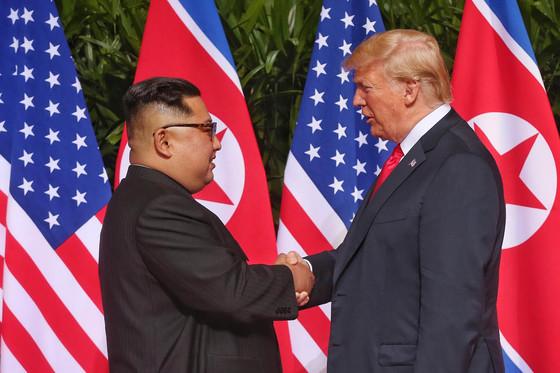 역사적 첫 북미정상회담이 열린 12일 오전 회담장인 카펠라 호텔에 북한 김정은 위원장과 미국 트럼프 대통령이 회담을 위해 만나고 악수를 나누고 있다. (싱가포르 통신정보부 제공)