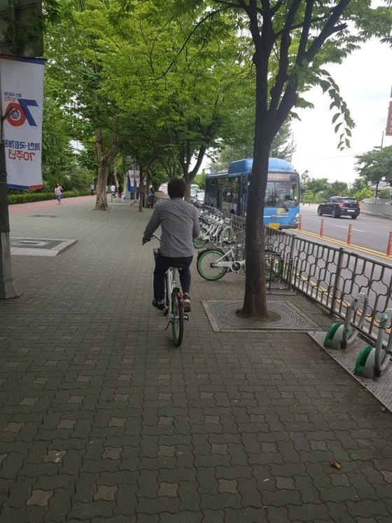 서울 여의나루역 1번 출구 앞에서 한 시민이 헬멧을 쓰지 않고 따릉이를 타고 있다. [임선영 기자]