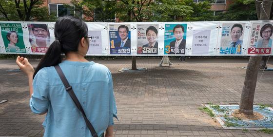 제7회 전국동시지방선거를 하루 앞둔 12일 한 시민이 서울 용산구 인근에 설치된 선거벽보를 살펴보고 있다. [뉴스1]