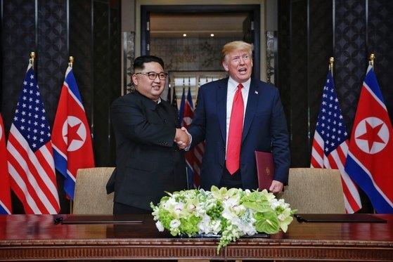 김정은 북한 국무위원장과 도널드 트럼프 미국 대통령이 12일 싱가포르 센토사 섬 카펠라 호텔에서 북미정상회담 공동합의문에 서명을 마친 뒤 악수를 나누고 있다. [뉴스1]
